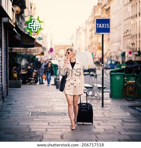 Young woman with cigarette walking in the street of Paris, France. Full body portrait. - stock photo