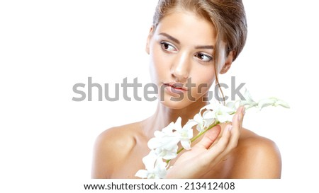 Young woman with clear face natural make up her hair up with a white flower on a light background