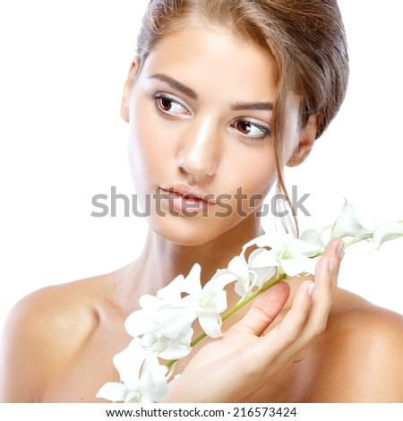 Young woman with clear face natural make up her hair up with a white flower on a light isolated background