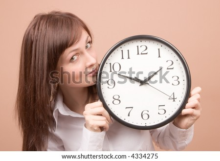 Young woman with clock isolated on beige background
