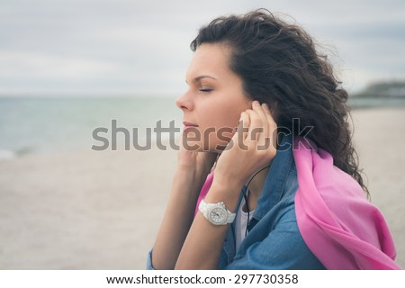 Young woman with closed eyes listening to music with headphones on the beach. She sitting on  sand and breathe the fresh sea air, she is dressed in a denim shirt on her shoulders pink cape. Soft light