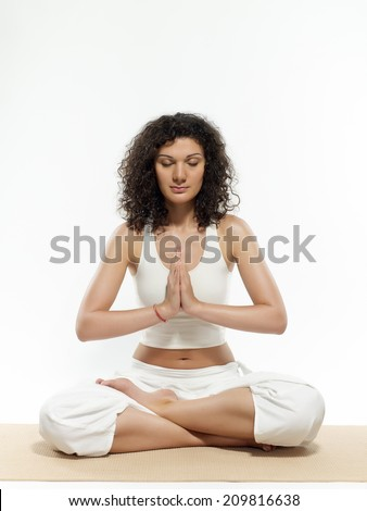 Young woman with closed eyes sitting in lotus position - stock photo