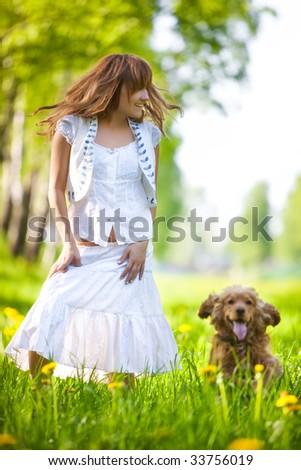 Young woman with cocker spaniel dog in a park. Focus on woman.