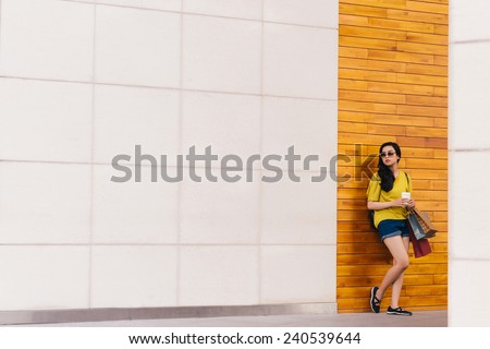 Young woman with coffee cup and paper bags standing at wall - stock photo
