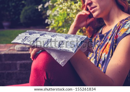 Young woman with cold pack on injured hand - stock photo