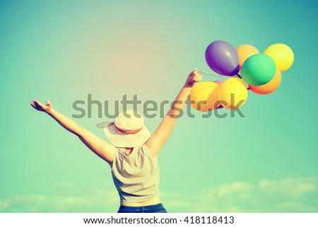 Young woman with colorful balloons in summer field - retro styled photo