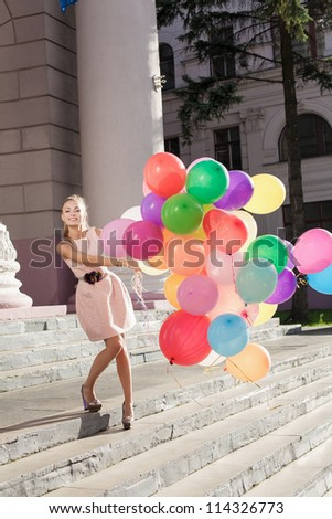 Young woman with colorful balloons, urban scene, outdoors