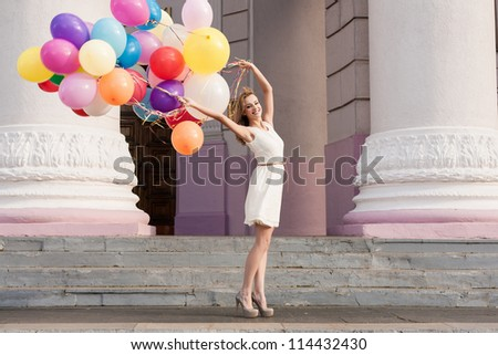 Young woman with colorful latex balloons keeping her dress, urban scene, outdoors - stock photo