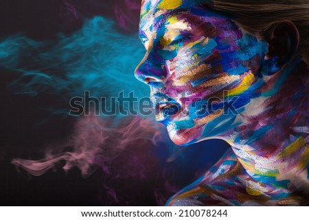 Young woman with colorful make-up and body art on a black background with multi-colored smoke - stock photo