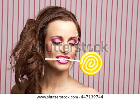 Young woman with colorful makeup and star candy glued to her face, holding an orange lollipop by the stick between her teeth - stock photo