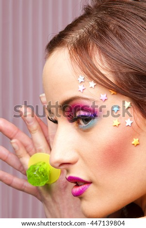 Young woman with colorful makeup and star candy glued to her face, showing a lollipop ring - stock photo