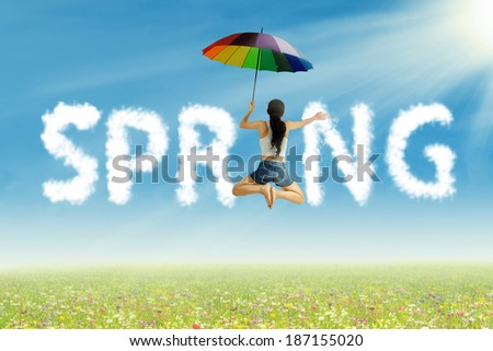 Young woman with colorful umbrella having fun on spring - stock photo