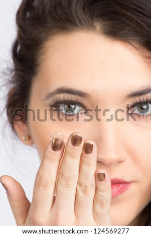 Young woman with contact lense, focused on lens, isolated on white