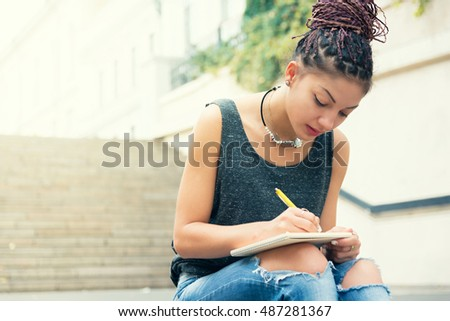 young woman with cornrows sitting on the chairs outdoors writting notes