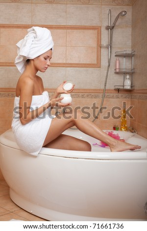 Young woman with cosmetic cream in a bathroom. Concept body care.