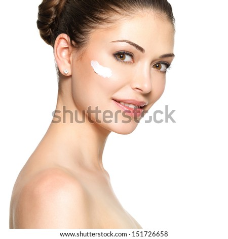 Young woman with cosmetic  cream on a clean fresh face - stock photo