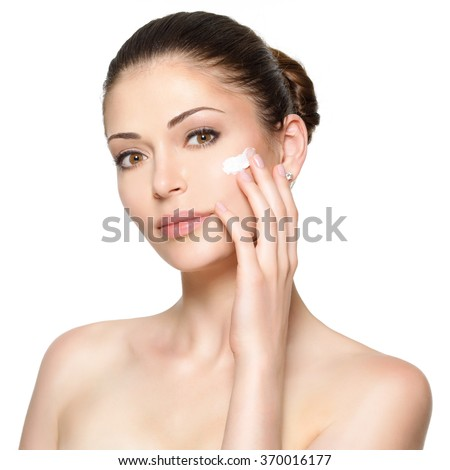 Young woman with cosmetic  cream on a clean fresh face. Skin care concept