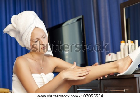 Young woman with cosmetic lotion in a bedroom. Concept body care. She is applying moisturizer cream on her slim legs - stock photo