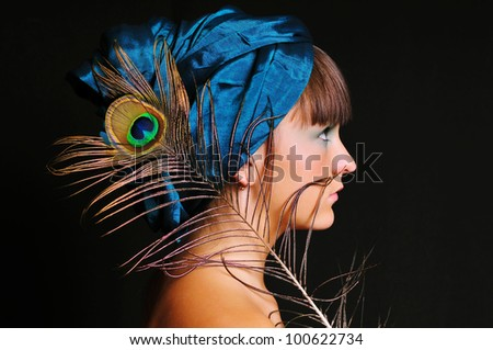 Young woman with creative make-up in blue turban with peacock feather - stock photo