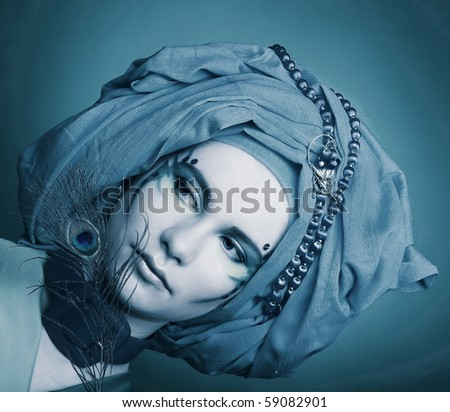 Young woman with creative make-up in blue turban with peacock feathers