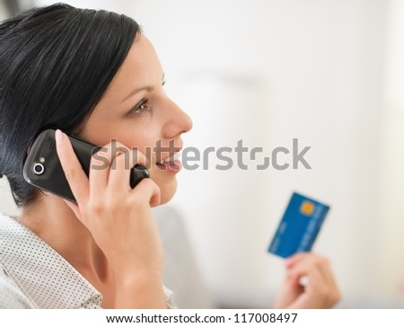 Young woman with credit card and speaking mobile phone