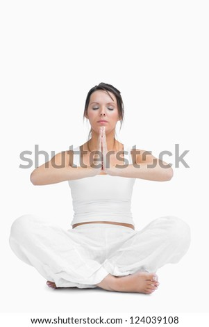Young woman with crossed legs in praying position over white background - stock photo