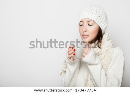 Young woman with cup in white clothes and hat on white background  - stock photo