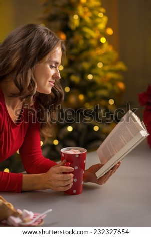Young woman with cup of hot chocolate reading book in front of christmas tree - stock photo
