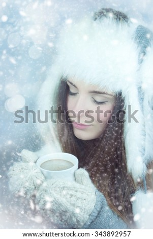 Young woman with cup on winter holiday background.
