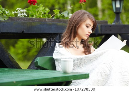 Young  woman with cup outdoors - stock photo