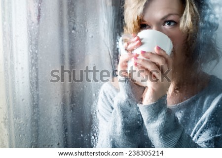Young woman with cup throw the rain drops - stock photo