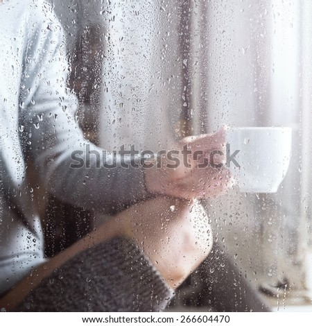 Young woman with cup throw the rain drops