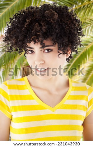 Young woman with curly hair and shirt with yellow stripes. Work Path. - stock photo