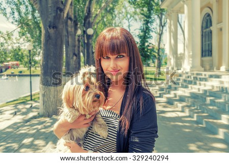 Young woman with cute decorative dog on her hands resting in city park - stock photo
