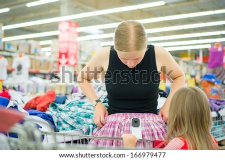 Young woman with daughter select skirts and clothes in supermarket