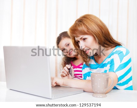 Young woman with daughter using laptop computer at home