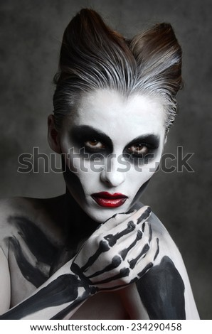 Young woman with dead mask skull face art. Halloween face - stock photo