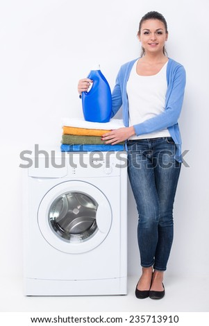 Young woman with detergent and laundry near the washing machine on the white background.