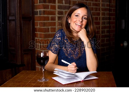young woman with diary and wine - stock photo
