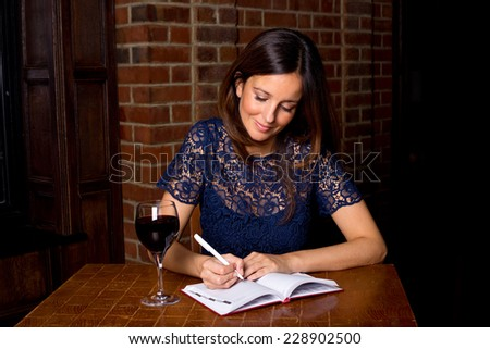 young woman with diary and wine