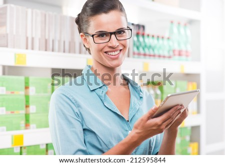 Young woman with digital tablet and stylus at supermarket with store shelves on background. - stock photo