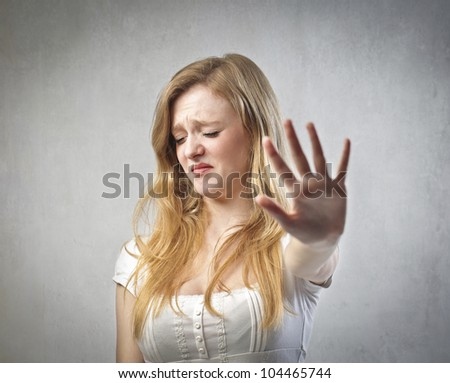 Young woman with disgusted expression repulsing something - stock photo