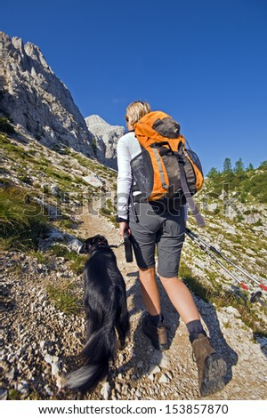 Young woman with dog on a sunny day hiking in high mountains - stock photo