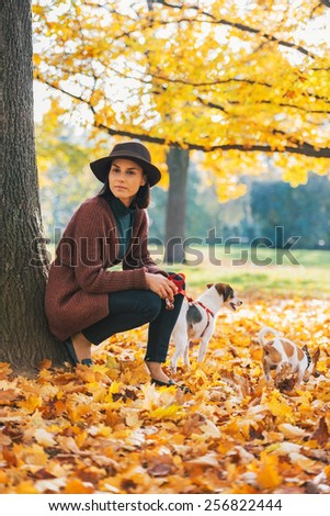 Young woman with dog standing outdoors in park in autumn - stock photo