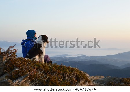 Young woman with dog watching sunrise high in the mountain, Rila Mountains, Bulgaria - stock photo