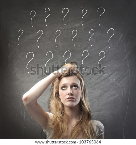 Young woman with doubtful expression and question marks over her head