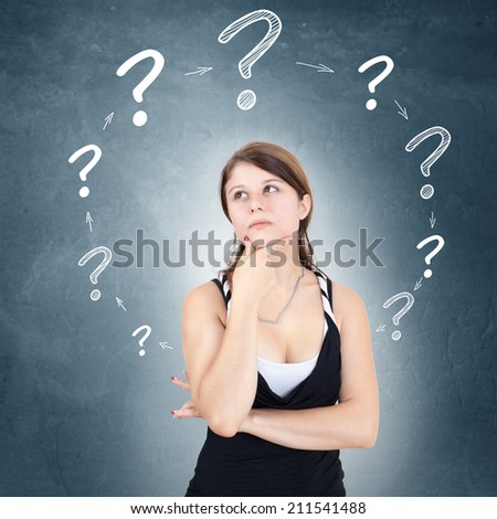 Young woman with drawn question marks circulating around her head - stock photo