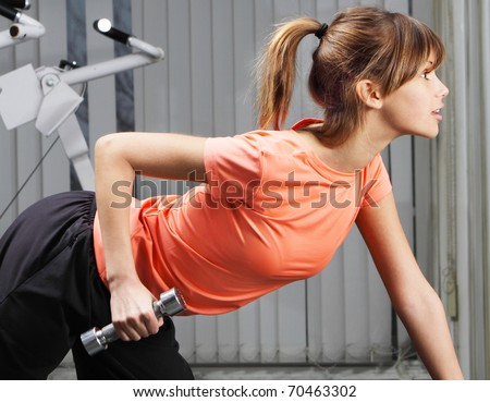 Young woman with dumbbell in fitness club