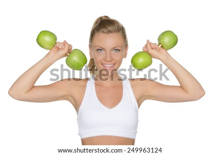 Young woman with dumbbells from ripe apples isolated on white - stock photo