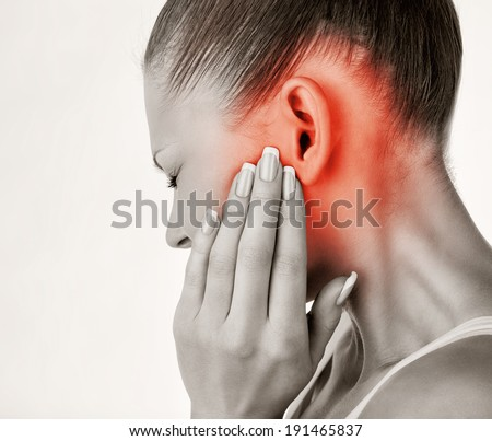 Young woman with ear pain, holding hand on his head on white background